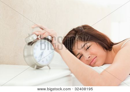 A woman is silencing the ringing bell of the alarm clock on the table beside the bed, with her hand. She is also only half awake.