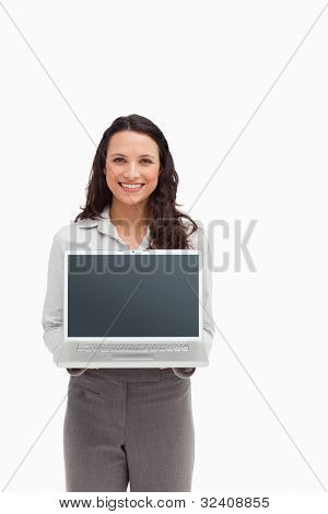 Smiling brunette standing while showing a laptop screen against white background