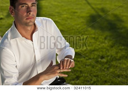 Pensive young man touching his wedding ring, maybe not sure of his choice