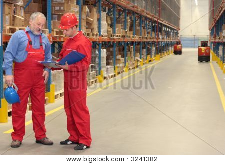Workers Checking Invoice In Warehouse