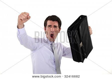 happy businessman raising his briefcase and fist