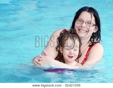 Happy family swimming in a pool.