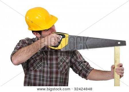 A carpenter with a handsaw.