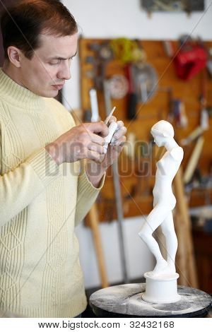 Sculptor works attentively in the studio on a fragment of the plaster sculpture.