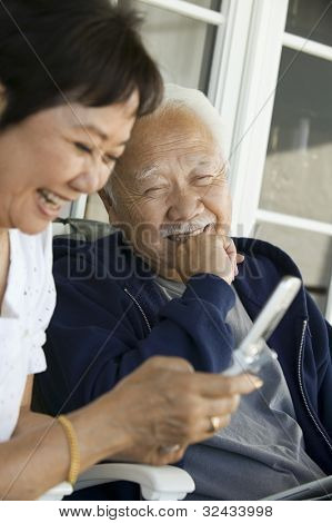 Smiling Couple Using Cell Phone