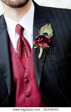 a red boutonniere corsage with a peacock feather design