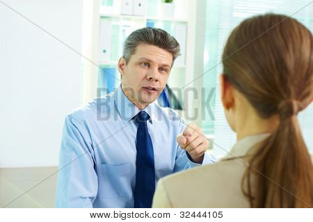 Businessman pointing at his female associate as if accusing her