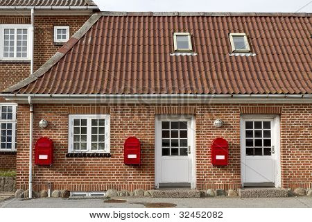 Red Mailboxes On Stone Walled House