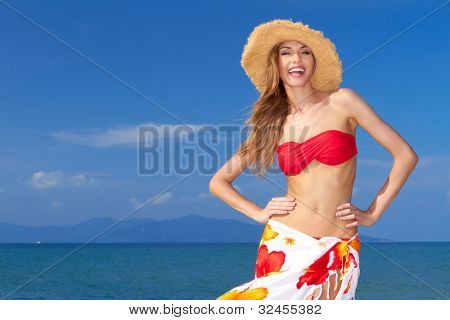High-spirited beautiful woman laughing in merriment as she poses in front of the ocean in her bikini and colourful sarong