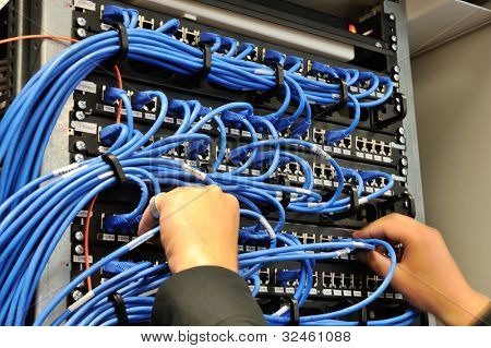 Man connecting network cables to switches