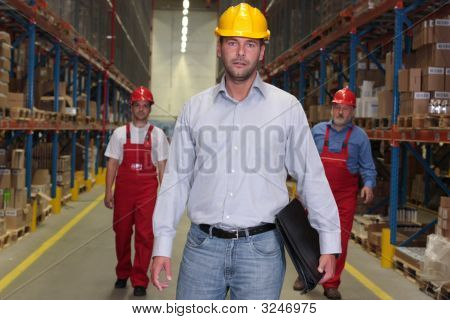 Engineer In Hardhat At The Front Of Workforce In Warehouse