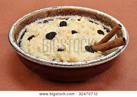 Large Bowl Of Creamy Rice Pudding With Raisins And Cinnaomon Sticks.