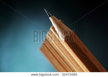 One sharpened pencils in row with pencil ends,