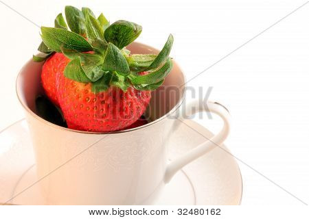Fresh Red Strawberries in White China Teacup with Saucer on Plai