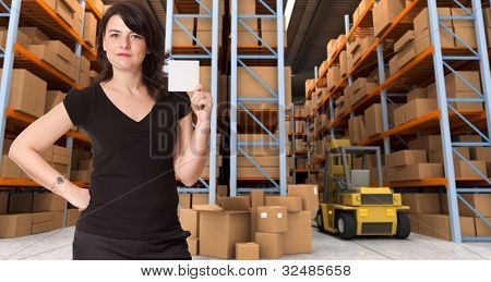 A woman holding a blank paper in a distribution warehouse, ideal for inserting your own message