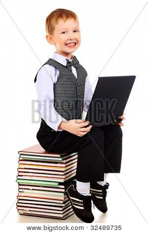 Shot of a boy learning with his books and laptop. Isolated over white background.