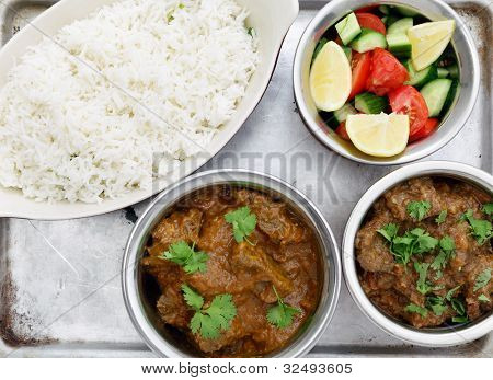 High angle view of a Madras butter beef curry (centre bottom) and ordinary curried beef with salad and rice, on an aluminium tray seen from above