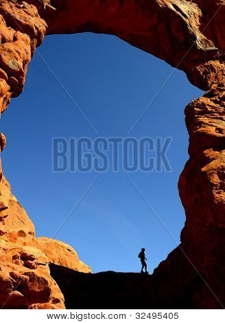 Silhouette of person hiking in Arches National Park
