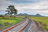 Old Railway Tracks Running Through A Field Stretch To Rural Countryside At Sunset. Single Railway Tr poster
