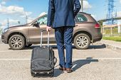 Man In A Blue Suit With A Suitcase At The Airport Parking On The Backdrop Of His Car. Business Trip  poster