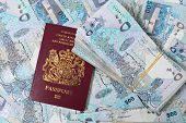 A British passport mixed in with a stash of high-value Qatari banknotes worth about $20,000 - a busi