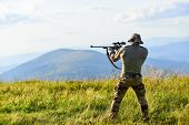 Nice Shot. Rifle For Hunting. Hunter Hold Rifle. Hunter Mountains Landscape Background. Focus And Co poster