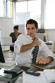 Man sat in office adjusting his tie