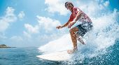 Young caucasian man surfs the ocean wave and makes a lot of splashes into the camera. Chickens surf  poster