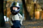 Funny Child With A Big Motorcycle Helmet On His Head. Helmet Boy poster