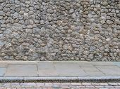 Natural Rough Stone Wall Texture Background With Concrete Slabs And A Curb On The Floor. Stone Wall  poster