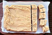 Whole Block Of Delicious, Homemade Peanut Butter Fudge Over A Rustic Wood Cutting Board Being Cut In poster