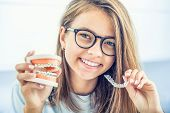 Dental Invisible Braces Or Silicone Trainer In The Hands Of A Young Smiling Girl. Orthodontic Concep poster
