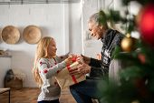 Happy senior woman giving christmas surprise to little girl at home. Excited granddaughter unpacking poster