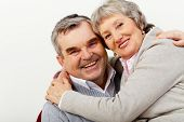 stock photo of old couple  - Portrait of a mature couple happily hugging and looking at cam - JPG