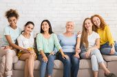 Group Of Diverse Women Smiling At Camera Sitting On Couch Against White Wall Indoor. Equality Concep poster