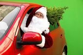 Authentic Santa Claus With Fir Tree Driving Car Against Green Background poster