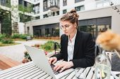 Young Business Woman Sitting At Coffee Shop On Veranda And Working On Laptop. Portrait Of Female Fre poster