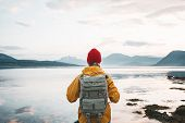 Alone Traveler Wearing Yellow Raincoat And Backpack Looking At Fantastic Fjord And Mountain Landscap poster