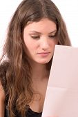 image of post-teen  - pretty brunette reading a bad news letter - JPG