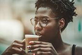 The Portrait Of A Young Charming African Female With Nail-art And In Spectacles Is Taking A Sip From poster