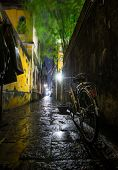 Wet bicycle stands near the wall on the narrow wet street in the town of Hoi An in Vietnam poster