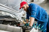 Bearded technician of car repair service with wrench examining engine of broken vehicle while bendin poster