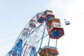 Giant Ferris Wheel With Colorful Empty Booths. Bottom View Of A Ferris Wheel And Blue Sky On A Sunny poster