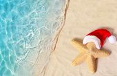 Christmas Holidays Concept. Top View Of Starfish In Santa Claus Hat On Summer Sand Beach poster
