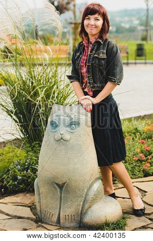 Young Woman Standing Near Funny Cat Statue