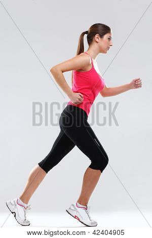 Young beautiful woman in fitness wear runs isolated over background
