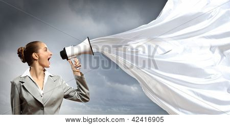 businesswoman in grey suit screaming into megaphone