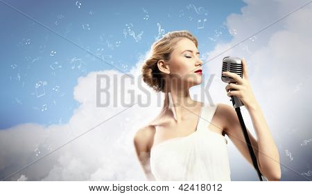 Image of female blonde singer holding microphone against clouds background with closed eyes