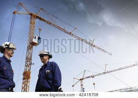 construction workers with mobile-cranes inside building site