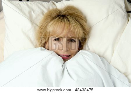 Woman Pulling Blanket To Her Face In  Fear